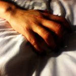 Picture of a hand grasping at a white bedsheet