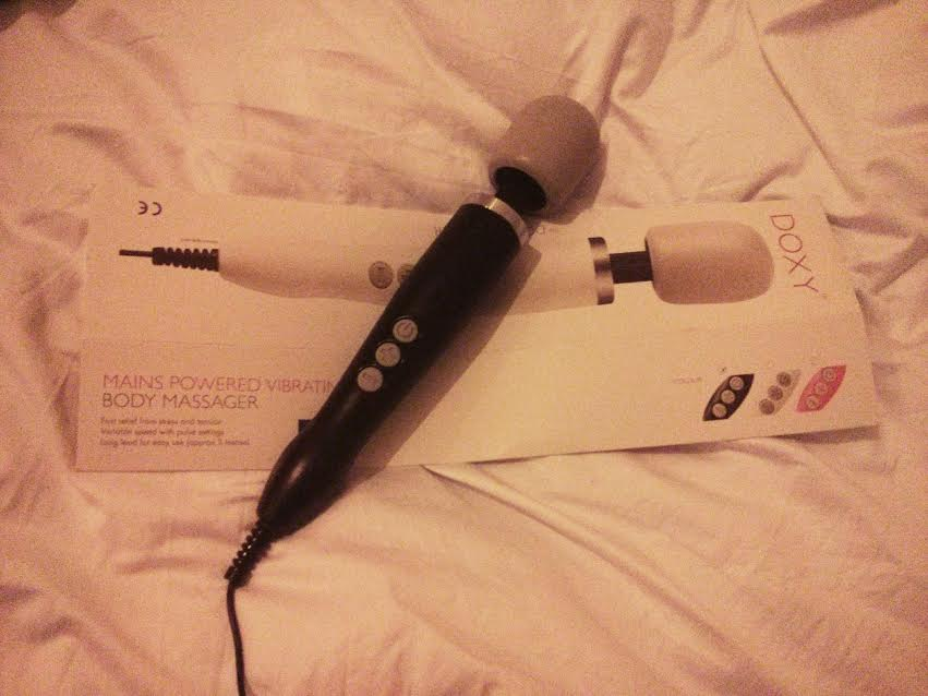 Picture of a Doxy massager - black bodied grey-headed wand-style sex toy, plus box, on white sheet