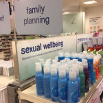 Image of Boots's lube section with a sign above that says 'sexual wellness' (good!) but just above that another sign says 'family planning' (bad)