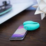 Picture of we vibe sync - a turquoise u-shaped sex toy - lying on top of an iphone on top of a desk