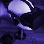 picture of an oculus rift virtual reality headset on a stand on a desk, the image is slightly tinted purple. The oculus rift may or may not be being used to watch vr porn (virtual reality porn)