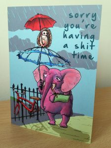 Card with a picture f an elephant and a hedgehog holding umbrellas on it that says 'sorry you're having a shit time'