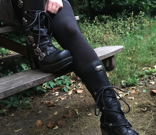 Girl wearing sexy boots in a super-goth style sits on a picnic bench near some grass