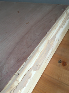 Picture of the side of table top with messy wood filler spilling out of the gaps and cracks