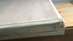 Corner of table top, with hardened wood filler spilling over it
