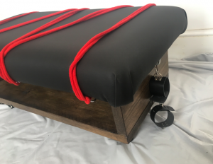 Corner view of spanking bench, with ropes and handcuffs attached to the mount points
