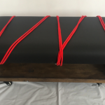 Coffee table with customised wipe-clean pleather top, and mount points with red rope and handcuffs attached to it
