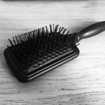 Square paddle-style hairbrush (exactly the kind I'd like to get spanked with) sits on wooden desk - photo is in black and white
