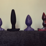 Four butt plugs lined up on the back of a sofa all ready for butt plug training - purple sparkly and small, slim and black, purple sparkly and medium sized, and red/silver silicone with two nubs instead of one