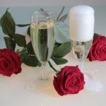 Two champagne flutes with red roses nearby