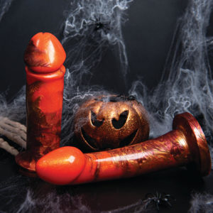 Orange and black dildos next to a pumpkin