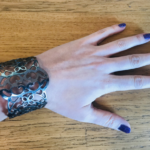 Image of a hand with purple nail varnish wearing a chunky silver bracelet (the bracelet means 'tear off my clothes'