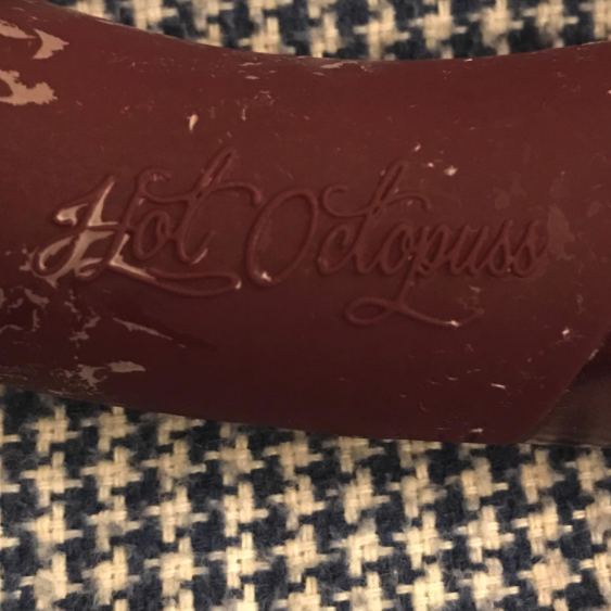 Image of the Hot octopuss logo embossed on the side of a Kurve g-spot toy, with dried quim caked into the writing